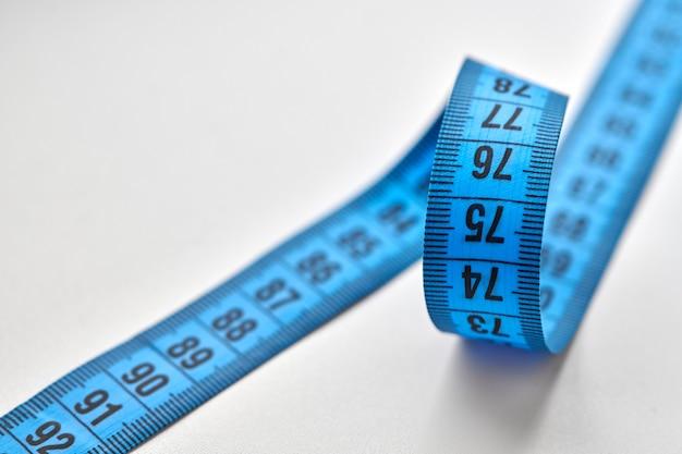 Nastro di misurazione blu isolato su sfondo bianco