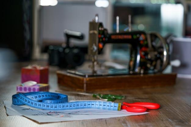 Nastro di misurazione blu e forbici con manico rosso su schizzi con abiti. schizzi del sarto, lavoro di progettazione. progetto con bei vestiti sul tavolo. concetto di sarto. avvicinamento.