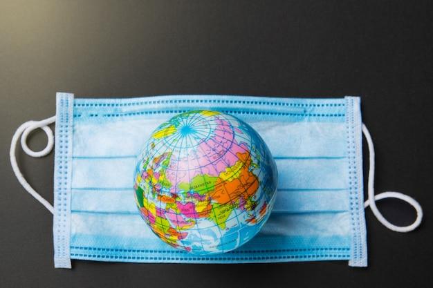 Su una fasciatura blu medica si trova un modello del pianeta terra, il concetto dell'epidemia globale di virus