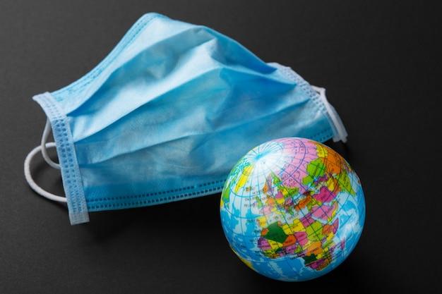 Maschera medica blu e mock up del pianeta terra, concetto di protezione della popolazione del pianeta dal coronavirus