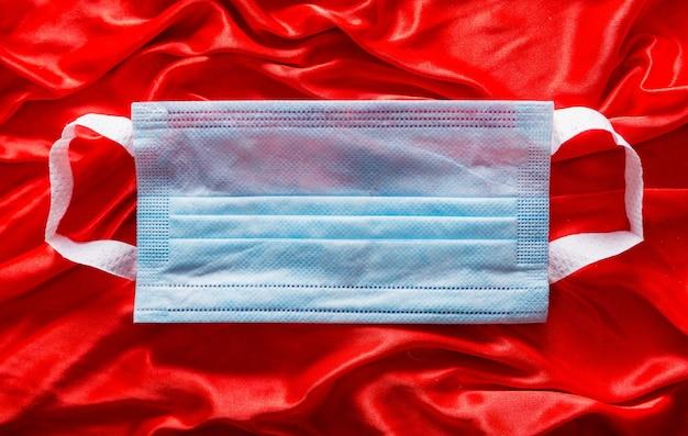 Maschera medica blu su tessuto di seta rosso