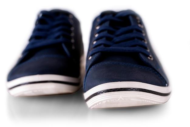 Le scarpe da ginnastica estive degli uomini blu isolate su bianco. messa a fuoco selettiva