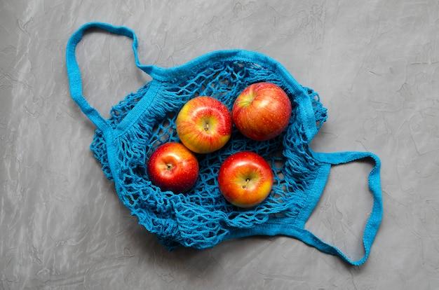 Shopping bag eco zero in rete blu con mele rosse frutta