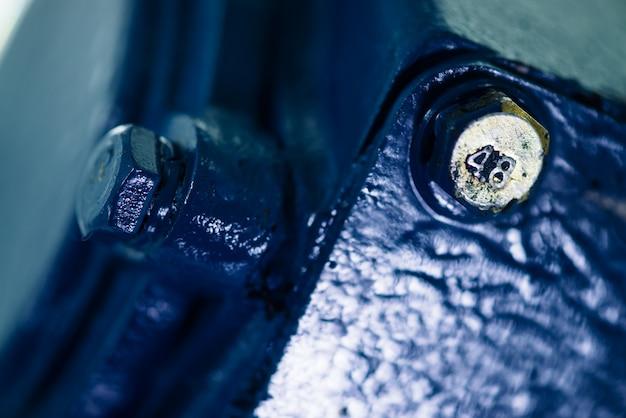 Superficie ruvida del metallo blu della parte con bullone d'oro. verniciato in blu di ricambi auto.