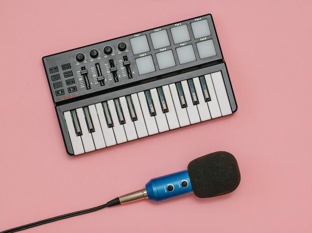 Microfono blu con fili e mixer musicale sulla superficie rosa. la vista dall'alto.