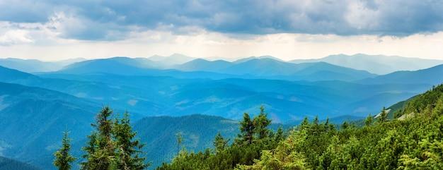 Montagne blu ricoperte di foresta verde. vista panoramica della cresta dei picchi