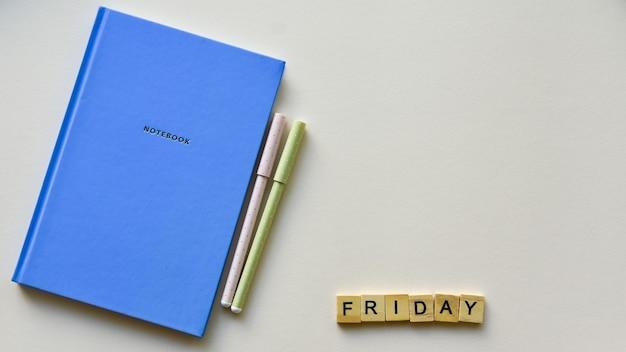 Quaderno blu con due penne e scritta in legno