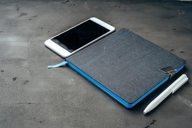 Blocco note blu, smartphone e penna sul tavolo grigio scuro