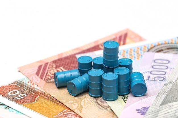 Tamburi di petrolio blu e banconote di carta su fondo bianco