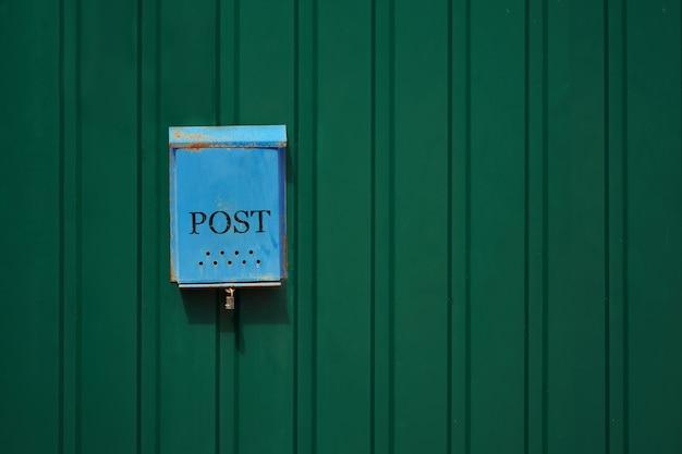 Vecchia cassetta postale arrugginita blu sulla recinzione metallica verde con uno spazio di copia