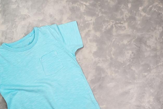 Maglietta di vernice blu con spazio di copia. mockup di t-shirt, piatto lay. sfondo concreto moderno.
