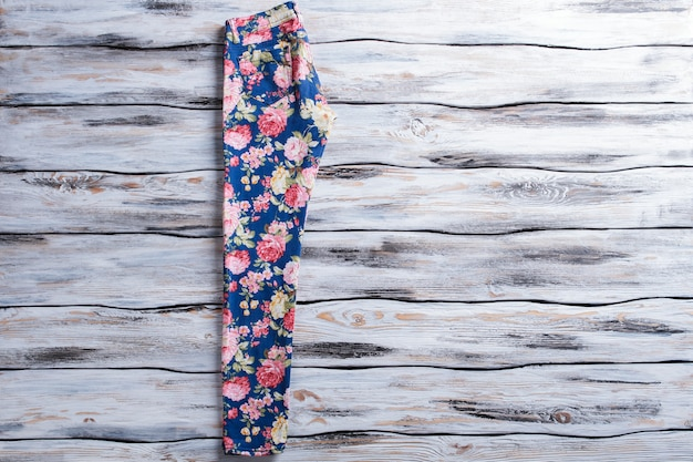 Pantaloni blu con motivo floreale. pantaloni floreali su fondo in legno. pantaloni da donna con stampa alla moda. abbigliamento popolare in vendita.