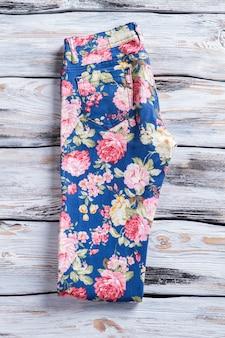 Pantaloni blu con stampa floreale. pantaloni alla moda su fondo di legno. articolo nuovo a prezzo speciale. sconti per abbigliamento bambina.