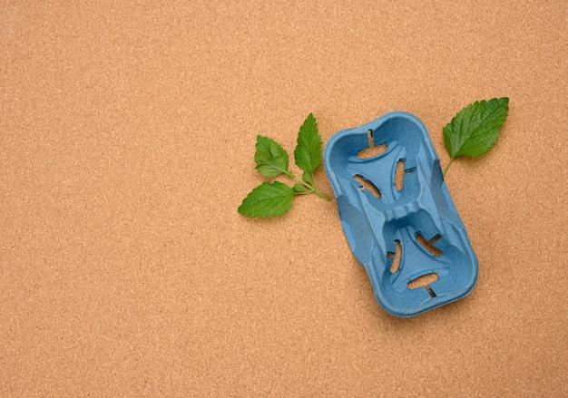 Porta carta blu per due bicchieri riciclati e foglie di menta verde su una superficie marrone. il concetto di evitare la plastica, preservare l'ambiente, vista dall'alto