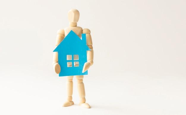 Casa di carta blu nelle mani di un uomo di legno, concetto di assicurazione immobiliare