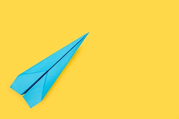 Un aereo di carta blu su sfondo giallo con spazio di copia