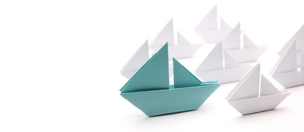 Nave di carta blu con piccole barche.concetto di leadership.