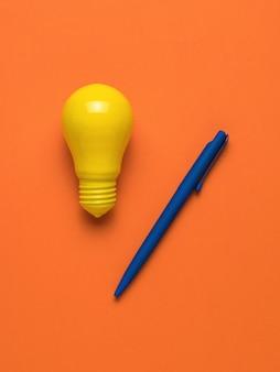 Una penna blu e una lampadina gialla brillante su uno sfondo arancione. disposizione piatta.