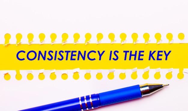 Penna blu e strisce bianche di carta strappata su uno sfondo giallo brillante con il testo la coerenza è la chiave