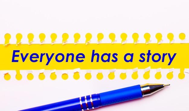 Penna blu e strisce bianche di carta strappata su uno sfondo giallo brillante con il testo tutti hanno una storia