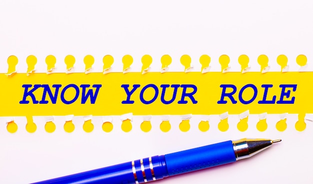 Penna blu e strisce bianche di carta strappata su uno sfondo giallo brillante con il testo conosci il tuo ruolo