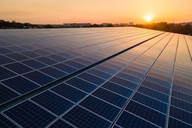 Pannelli solari fotovoltaici blu montati sul tetto dell'edificio per la produzione di elettricità ecologica pulita al tramonto. produzione del concetto di energia rinnovabile.