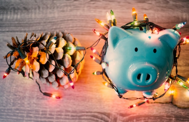 Salvadanaio blu e pigna con luci per feste, goditi i risparmi per il concetto di vacanze.