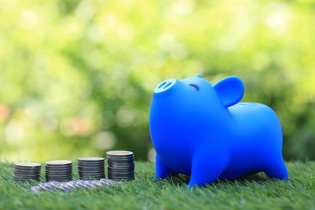 Salvadanaio blu e pila di monete soldi su spazio verde naturale