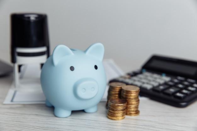 Salvadanaio blu, timbro e monete sulla scrivania in legno in ufficio. risparmiare denaro e concetto finanziario di gestione