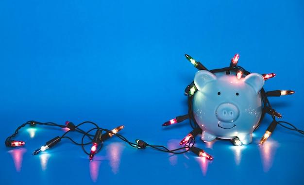 Salvadanaio blu con luci natalizie su un felice festival di dicembre, risparmia per spendere soldi per il concetto di vacanza.