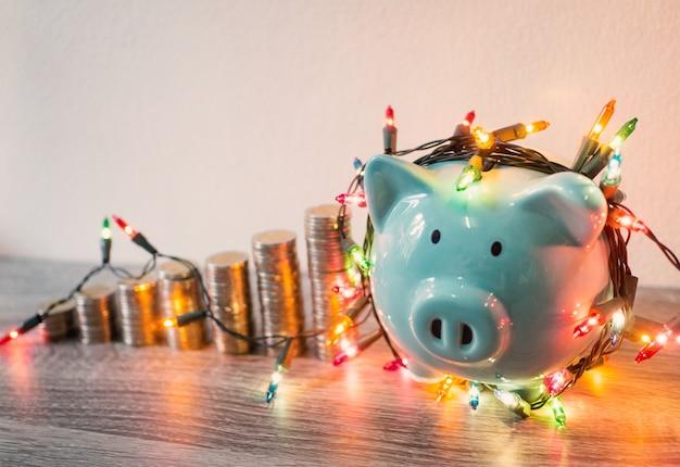 Salvadanaio blu con grafico di crescita del mucchio di monete e luci di festa, risparmio di denaro divertente per il futuro piano di investimento e concetto di fondo pensione