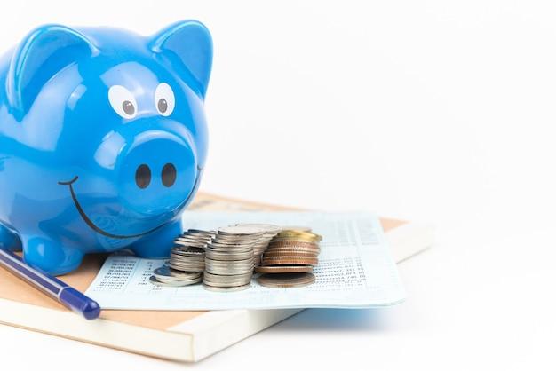 Salvadanaio blu con pila di monete sul libro dei conti aperto risparmio finanziario e concetto di ricchezza di denaro