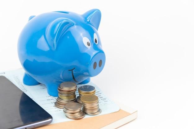 Salvadanaio blu con matita e monete in pila sul libro dei conti vicino con sfondo del telefono cellulare Foto Premium