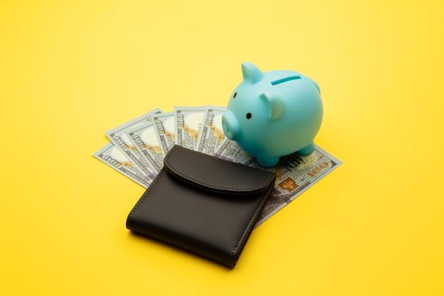 Salvadanaio blu con un portafoglio con banconote da cento dollari su uno sfondo giallo. budget familiare, risparmio.
