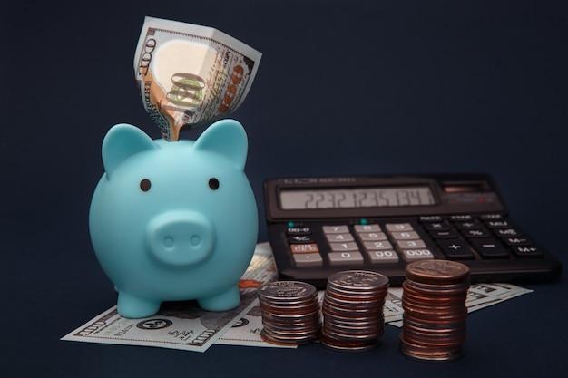 Un salvadanaio blu, soldi e calcolatrice su blu scuro.