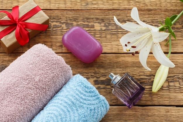 Asciugamani in morbida spugna blu e rosa con una bottiglia di profumo, sapone, una confezione regalo e fiori di giglio bianco sulle vecchie tavole di legno. vista dall'alto.