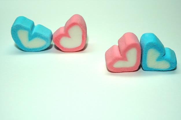 Cuori di caramelle dolci blu e rosa per san valentino su sfondo bianco