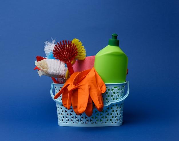 Cestino di plastica blu con spazzole, spugne e guanti di gomma per la pulizia, sfondo blu
