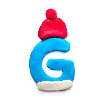Lettera g di plastilina blu dell'alfabeto in cappello rosso di inverno su priorità bassa bianca
