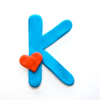 Alfabeto inglese lettera k di plastilina blu con cuore rosso che significa amore