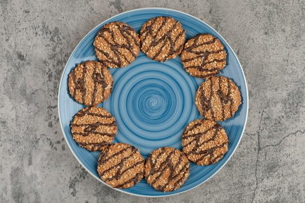 Piatto blu di biscotti con semi e cioccolato su marmo.