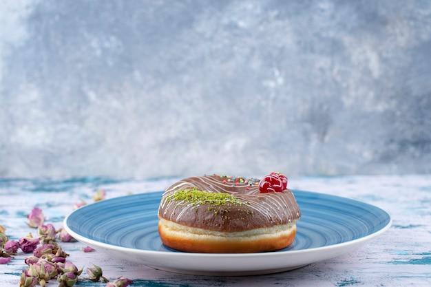 Piatto blu di ciambella fresca al cioccolato delizioso con ciliegia e granelli colorati.
