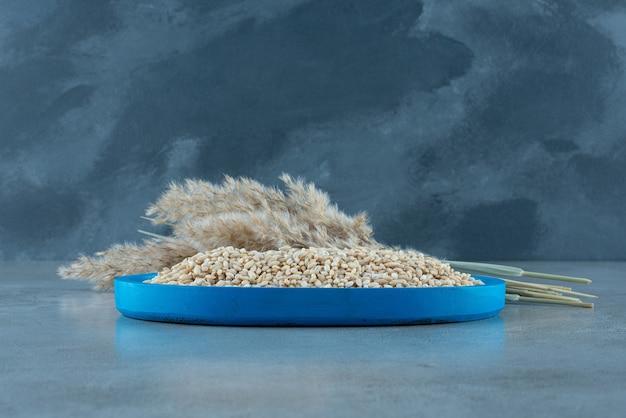 Piatto blu di riso crudo sulla superficie di pietra