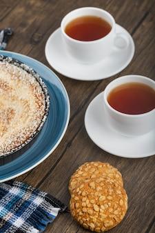Piatto blu di torta dolce con granelli di cocco, tazza di tè e biscotti su una superficie di legno