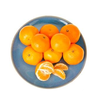 Piatto blu con mandarini arancioni luminosi isolati su priorità bassa bianca. foto di studio