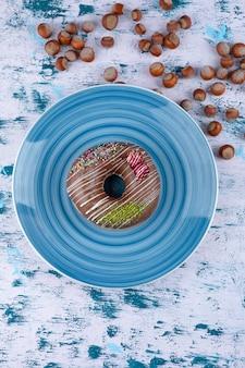 Piatto blu con ciambella al cioccolato e nocciole sgusciate su superficie bianca.