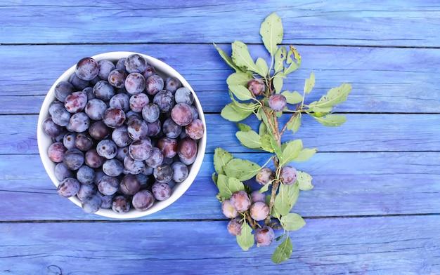 Prugne blu in giardino in una tazza su tavole di legno invecchiate