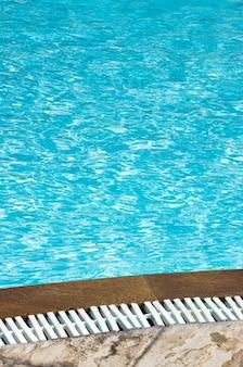 Acqua blu della piscina con riflessi del sole