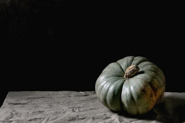 Zucca blu sulla tovaglia di lino. natura morta oscura. raccolto autunnale. copia spazio