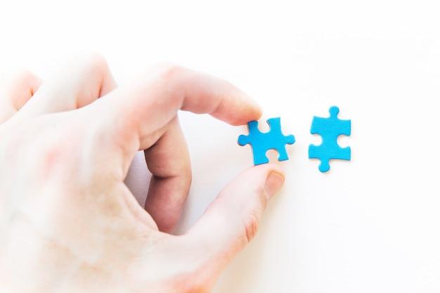 Puzzle blu in mano. mano che tiene il pezzo del puzzle. collegamento di un pezzo di puzzle, relazione d'affari, istruzione, società e lavoro di squadra